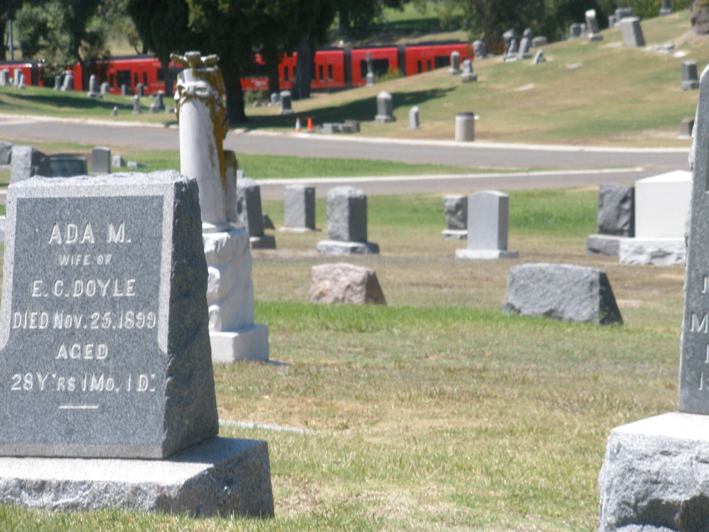 Ada Doyle's grave at Mt. Hope Cemetery, with red San Diego Trolley, following route of SDC&E, passing in background.