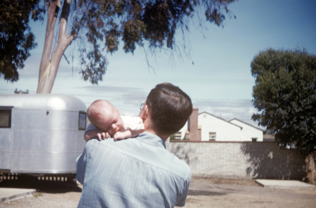 John C. Webster (and son) at the De Luxe Trailer Park, 4275 Cass Street, in 1948. The trailers and eucalyptus trees are long gone but the house across Dawes Street is still there.
